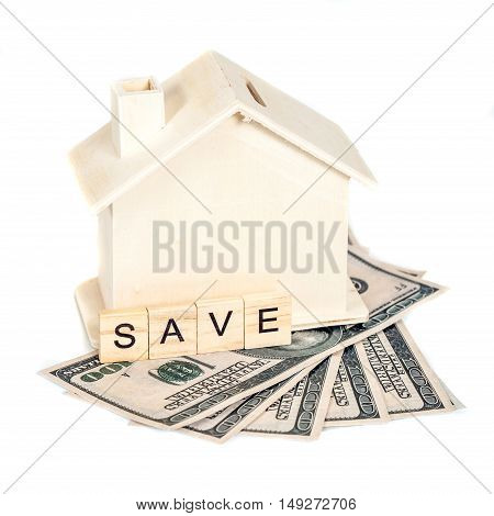 Miniature house with money on white background
