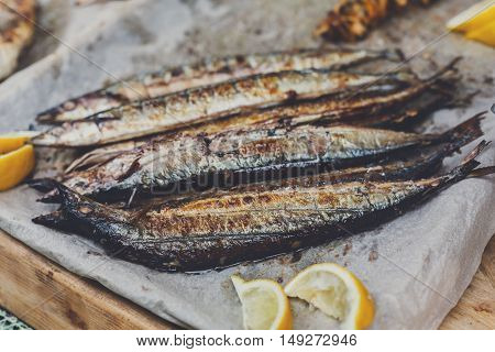 Plenty of roasted mackerel fish, grilled at barbecue. Seafood bbq outdoors at picnic, party. Street food, grill takeaway