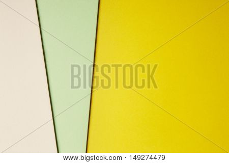 Colored cardboards background yellow green beige tone. Copy space. Horizontal