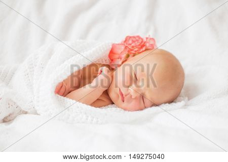 Baby tugged in white blanket with beautiful flower