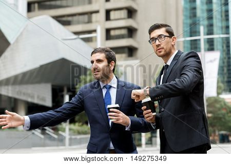 Two young businessmen hailing for a taxi