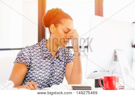 Portrait of tired afro-american office worker sitting in offfice