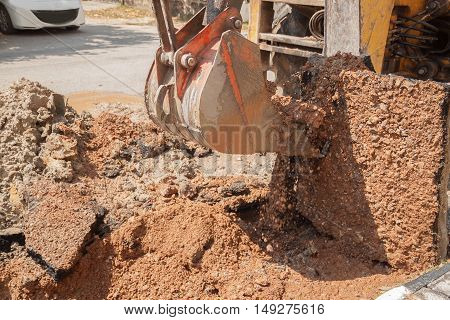 Excavator working on the Repair of pipe water and sewerage on road.