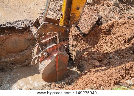 Excavator working on the Repair of pipe water and sewerage on road.(select focus on excavator and soft-focus motion water)