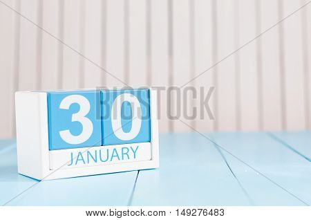 January 30th. Day 30 of month, calendar on wooden background. Winter at work concept. Empty space for text.