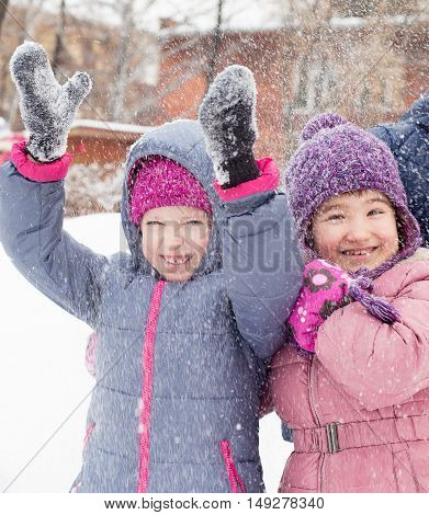 closeup portrait of Happy laughing children in winter clothes outside playing in the snow drifts in the winter - Russia Moscow - February 25 2016