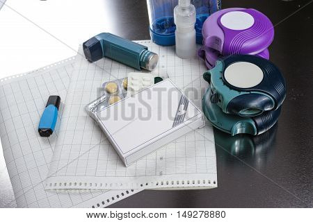 Asthma allergy, illness relief concept salbutamol inhalers aerosol medication drugs and paper on chrome background