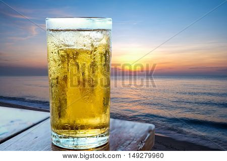 Glass of beer on the beach sea.