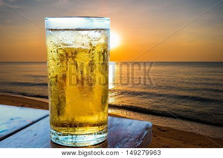 Glass of beer on the beach at sunset.