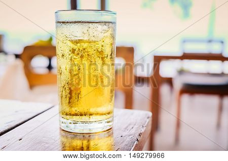 Glass of beer on wooden table in pub background.