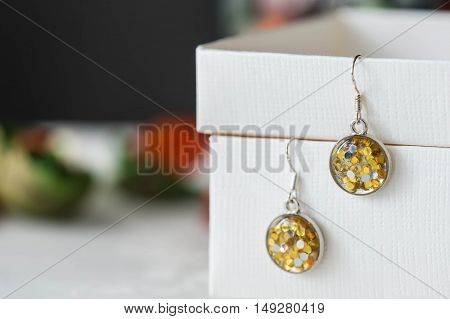Handmade Earrings Made Of Epoxy Resin And Yellow Glitter Closeup