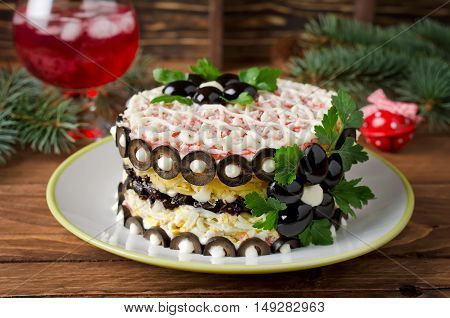 Salad with crab sticks cheese egg and prunes. Decorated with flowers made of olives
