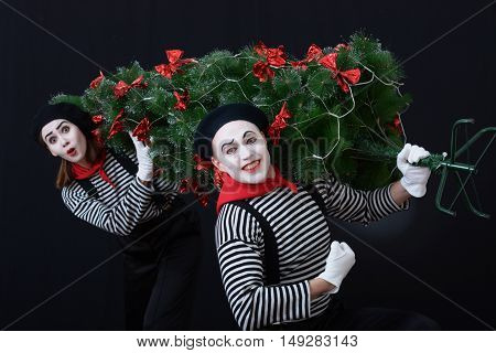 Two mime in striped shirt holding a Christmas tree