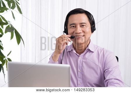 Portrait of handsome asian hotline person consultant wearing headset