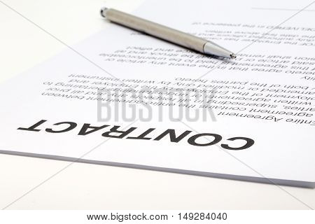 Close up of a contract and a silver pen in the background