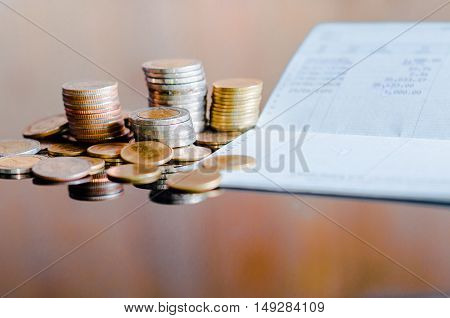 Thai banknotes and coins on book bank and account book background