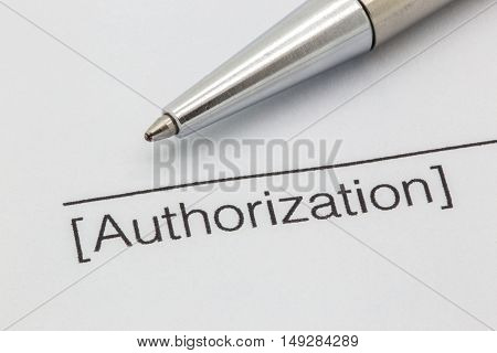 Close up of a contract with a line and the word authorization here and a silver pen