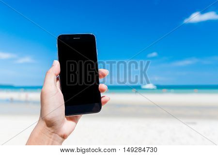 woman's hand using smart phone at beach. Smartphone black screen. Girl using black color smartphone at Beach from Thailand.