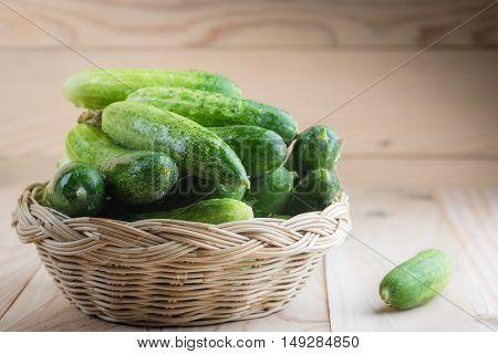 Fresh cucumbers in basket on wood .