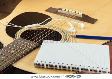Notebook and pencil on guitar Writing music
