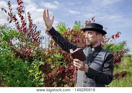 Young bearded priest holding book on leaves background