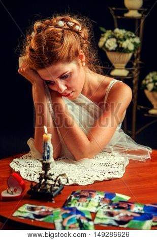 Sad woman suffers from failed marriage, she looked at pictures and holding his head. Wedding interior and wedding dress in the background. Are burning candle on table.