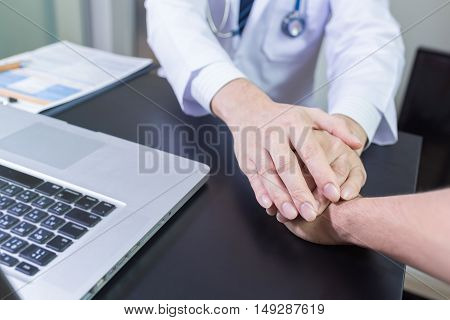 Doctor's Hands Holding  Patient's Hand For Encouragement And Empathy