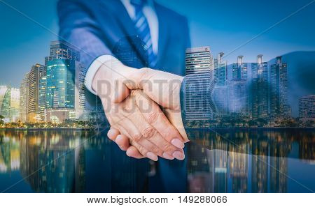 Business Man. Business handshake and business people on city background