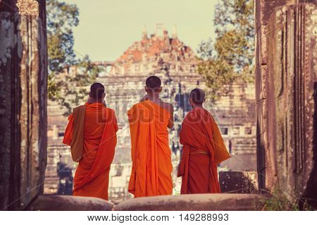 Buddhist monks in Ancient Khmer civilization ruins of Angkor near Siem Reap, Cambodia