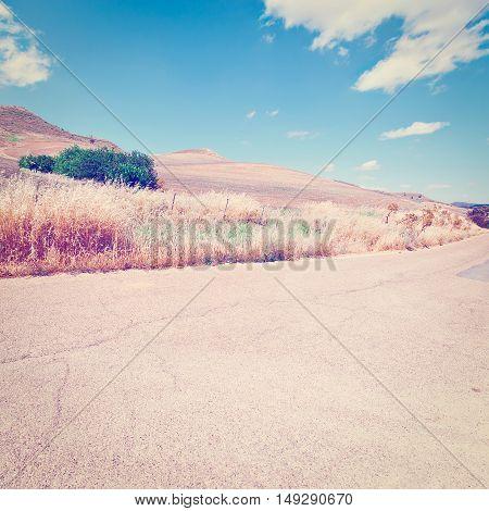 Asphalt Road between Wheat Fields on the Hills of Sicily Instagram Effect