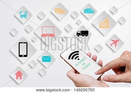 Internet of Things concept (IoT) with man hands holding smart phone in order to connect various devices smart machines and object icon Digital Marketing concept.