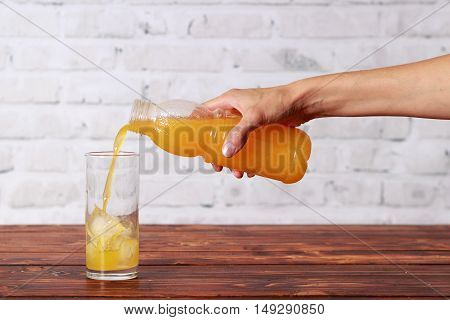 Girl's hand with bottle of orange juice pouring it in glass with ice cubes