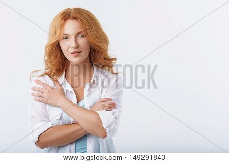 Sensual middle-aged woman is standing and looking at camera with gentleness. Her arms are crossed. Isolated and copy space in right side