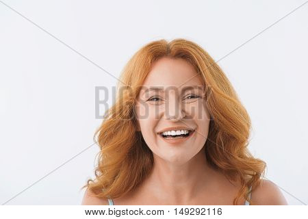 Joyful senior woman is standing and laughing. Isolated and copy space in left side