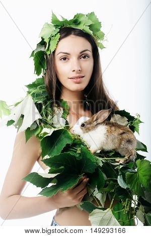 Beautiful woman young model in decorative green wreath of vine leaves poses with small rabbit isolated on white background