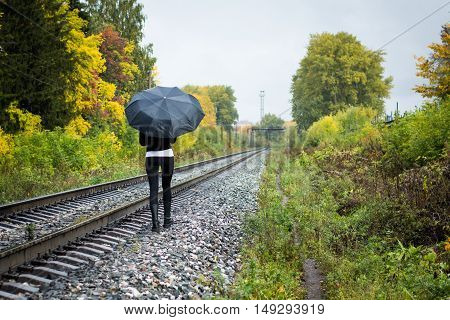 Girl, Umbrella And Rails In Autumn Day
