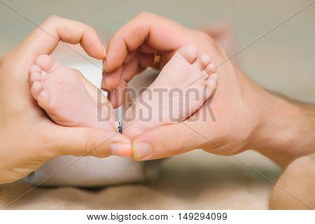 Newborn Feet In Parent Hands