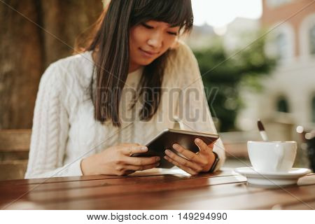 Chinese woman sitting with her digital tablet at outdoor cafe. Beautiful asian woman using touch screen computer.