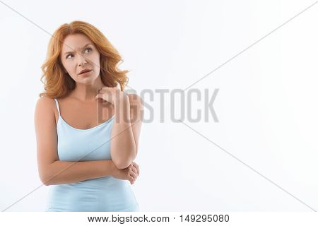 Middle-aged woman is standing and looking aside with surprise. Isolated and copy space in right side