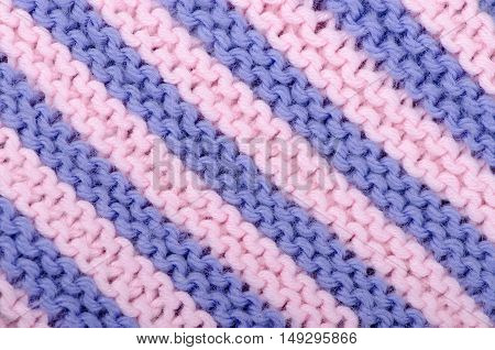 Knitted textile background of diagonal stripes of blue and pink