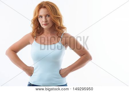 Serious middle aged woman is standing with arms akimbo. She is looking forward with irritation. Isolated and copy space in right side