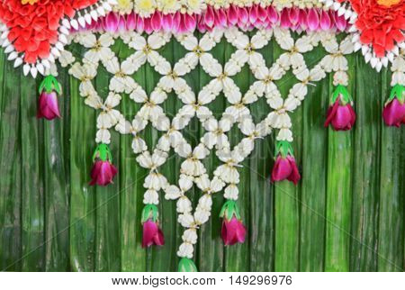 Blur blurred abstract  jasmine garland with pink rose on banana leaf for background