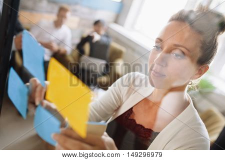 Woman Presenting Ideas To Colleagues During Meeting