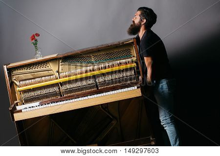 Bearded Man Trying To Move Wooden Piano With Rose
