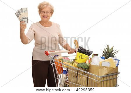 Happy elderly woman posing with a shopping cart full of groceries and stacks of money isolated on white background