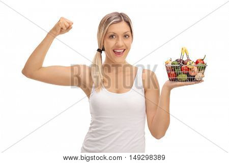 Smiling woman holding a small shopping basket full of fruits and groceries and flexing her bicep isolated on white background