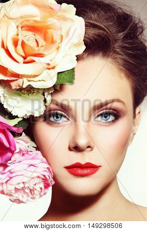 Close-up portrait of young beautiful woman with red lips and flowers near her face