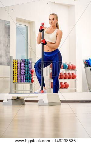 Sportive young woman with beautiful athletic body doing exercises with dumbbells. Fitness, bodybuilding. Healthcare.