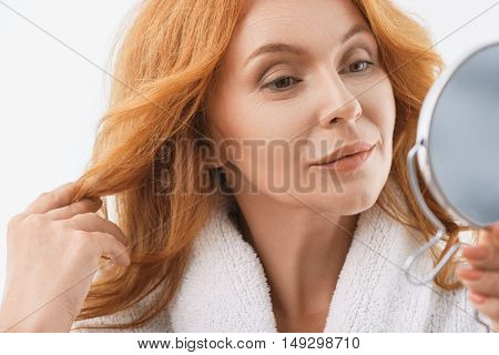 Pretty mature woman is satisfied with her skin reflection. She is holding mirror and gently smiling. Woman is standing in bathrobe and touching hair