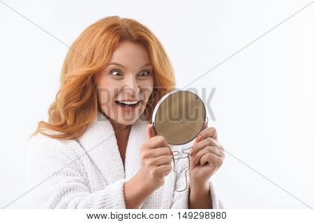 Happy middle-aged woman is looking at mirror with joy. She standing and laughing surprisingly. Isolated and copy space in right side